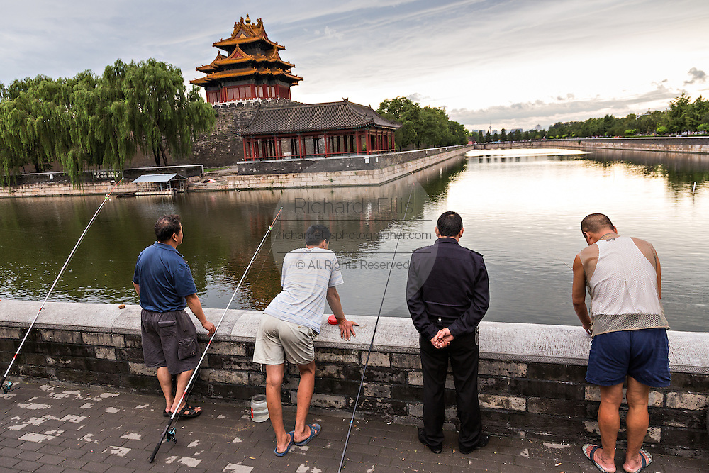 Beijing residents fish along the moat near the Arrow Tower on the palace walls of the Forbidden City during a summer evening in Beijing, China