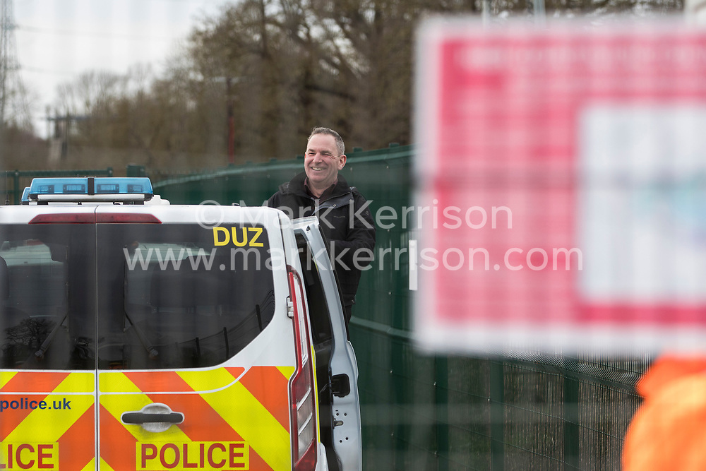 Harefield, UK. 18 February, 2020.  Partially-sighted former Paralympic cyclist James Brown of Extinction Rebellion smiles from a Metropolitan Police vehicle following his arrest at a HS2 site in the Colne Valley. He was arrested after locking himself with a fellow activist onto a drilling rig which environmental activists believe will be used to drill into the aquifer which supplies 22% of London's drinking water, risking contamination.