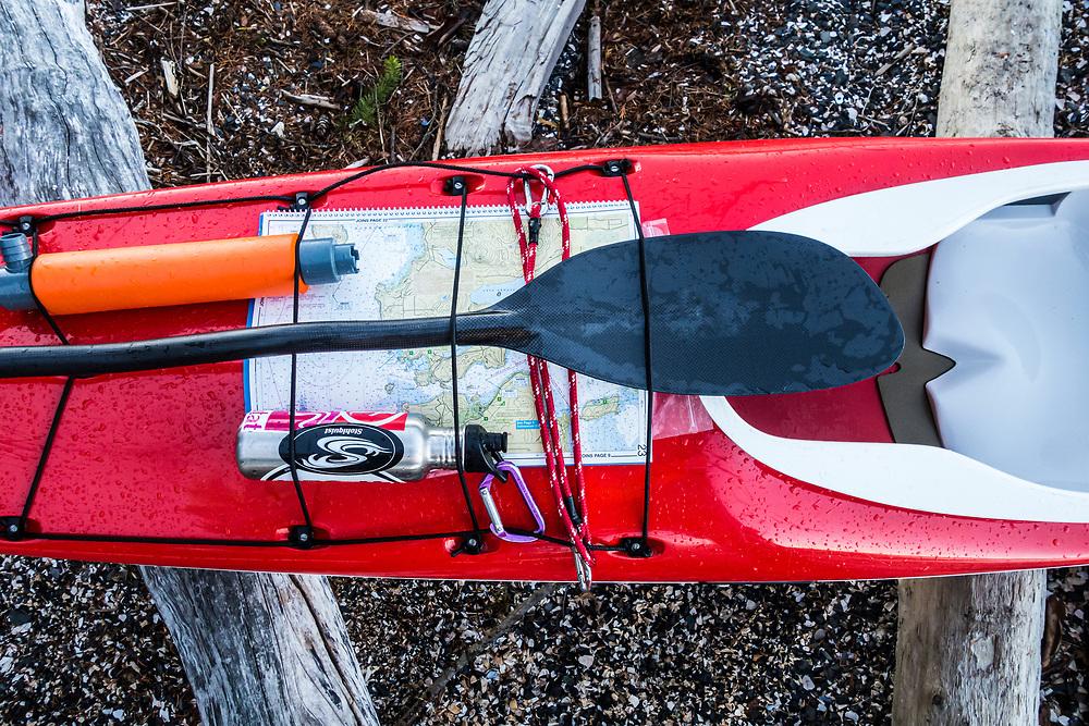Detail of maps and gear on a sea kayak. Skagit Island State Park, Washington, USA.