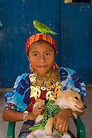 Kuna Indian girl in native costume (with Mola embrodery blouses) and dog in her village on Wichub Wala island, San Blas Islands (Kuna Yala), Caribbean Sea, Panama