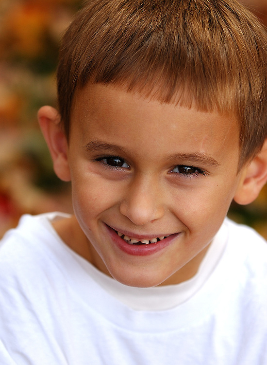 smiling caucasian child in white teeshirt against colorful autumn leaves