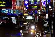 Hailing a Black taxi cab on Regent Street, London, United Kingdom