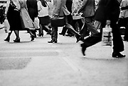 Feet of crowds hurrying to work in the forecourt outside Victoria station. Coming and Going is a project commissioned by the Museum of London for photographer Barry Lewis in 1976 to document the transport system as it is used by passengers and commuters using public transport by trains, tubes and buses in London, UK.