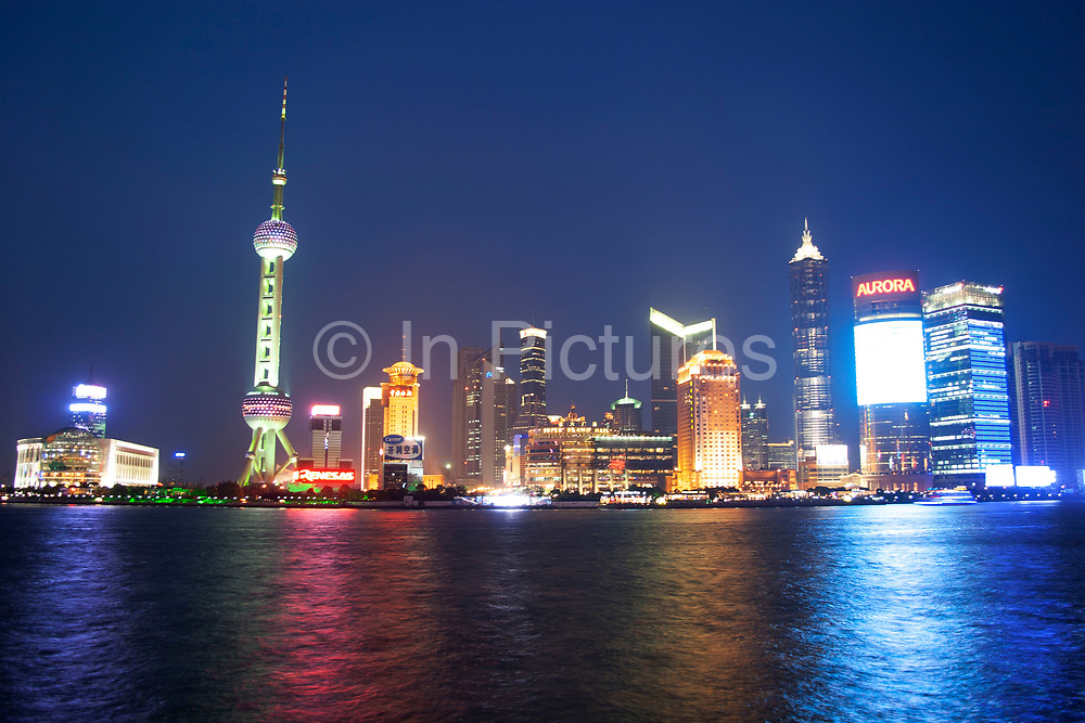 View across the Huang Pu River to Pudong and Lu Jia Zui financial district. At sunset as the light falls, this whole are comes to life, and the well known buildings stand out. The two dominant buildings are the Oriental Pearl Tower on the left and the Jin Mao Building on the right.This whole district has been developed from being low level Chinese housing since 1996-7.
