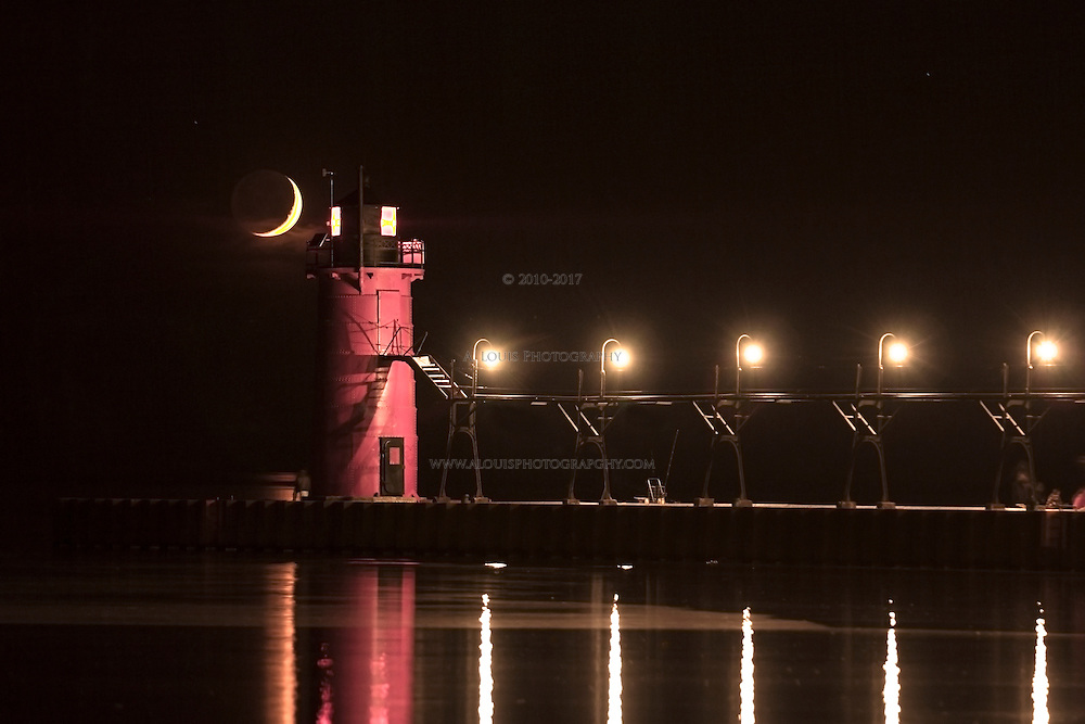 The setting crescent moon appears next to the South Shaven Lighthouse before it completes its decent onto a calm Lake Michigan