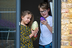 © Licensed to London News Pictures. 11/04/2020. London, UK. Olivia 9 and Louis 9 from Epsom in Surrey enjoy their Easter eggs while under lockdown as millions of children get used to staying in doors for long periods of time over the Easter holidays while the coronavirus pandemic continues. Photo credit: Alex Lentati/LNP