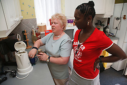 Woman with visual impairment with friend in kitchen.