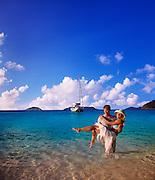 A man carries his wife through the surf at a crystal clear carribean beach
