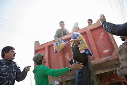 Licensed to London News Pictures. 11/11/2016. Mosul, Iraq. Residents of Mosul's Al Antisar district receive sacks of food from local volunteers. The Al Intisar district was taken four days ago by Iraqi Security Forces (ISF) and, despite its proximity to ongoing fighting between ISF and ISIS militants, many residents still live in the settlement without regular power and water and with dwindling food supplies.<br /> <br /> The battle to retake Mosul, which fell June 2014, started on the 16th of October 2016 with Iraqi Security Forces eventually reaching the city on the 1st of November. Since then elements of the Iraq Army and Police have succeeded in pushing into the city and retaking several neighbourhoods allowing civilians living there to be evacuated - though many more remain trapped within Mosul.  Photo credit: Matt Cetti-Roberts/LNP