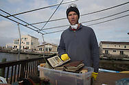 Michael Brune on the deck of his family home with a box of photo albums damaged by Superstorm Sandy in Chadwick Island Beach, NJ, November 18