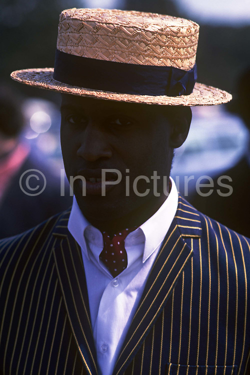 A very smart young man of afro-Caribbean descent wears a quintessentially English summer straw hat, cravat and pinstriped blazer during a hot afternoon at the Henley Royal Regatta boat races, England. He stands with the hat shading his dark-skinned face from a sun, while chatting to unseen friends. He appears to be a student at an English university – Oxford or Cambridge – and is here to take in the social scene at this famous boating event on the River Thames. In 1829 a boat race challenge was held between teams representing the universities of Oxford and Cambridge. The venue chosen was a straight stretch of the Thames at the small town of Henley-on-Thames. Now held July and is one of the main dates on the sporting calendar and social season for the hoi polloi.