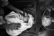 A young baby receives oxygen on a bench in the outside courtyard of a rural medical centre. The syringe next to the baby is dirty and already used. <br /> Lack of hygiene and proper medical care cause many of the neonatal deaths, making the neonatal mortality rate in Pakistan very high. In the villages hepatitus B and C is very common because of unsafe bloodtransfusions and unhygienic conditions in treating patients. Kandiaro, Pakistan 2010