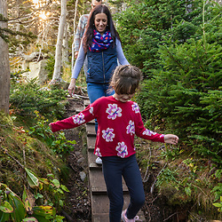 A couple hikes with their daughter on a trail at Quoddy Head State Park in Lubec, Maine.