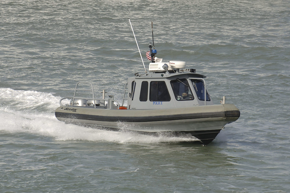 Port Aransas, TX January 15, 2006:  A harbor police boat works the Aransas Channel ahead of the USS San Antonio (LPD-17) amphibious transport dock after her commissioning ceremony 14 January 2006.   ©Bob Daemmrich /