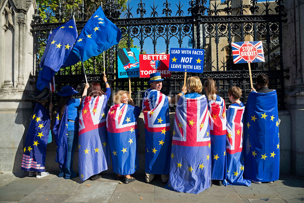 Anti Brexit protesters stand draped in EU and Union Jack flags outside the Houses of Parliament in London, United Kingdom on 12th September 2019.