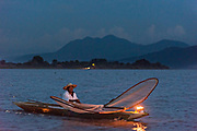 Indigenous Purépecha butterfly fisherman on Lake Patzcuaro at twilight near Janitzio Island, Michoacan, Mexico.