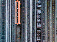 Aerial shot of railroad cars, one standing out with orange color, and tracks showing symmetry.