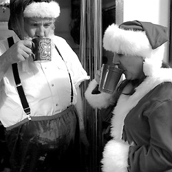 Russell Bissonnette and his partner Michelle Robelet drink tea in the kitchen of their Half Moon Bay apartment after his personal appearance as Santa Claus at the Miramar Beach Restaruant Christmas Party in Half Moon Bay on Monday night, Dec. 20, 2004.                               ..Photo by David Calvert<br />