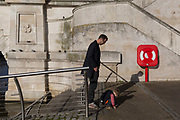 Next to a life buoy, a father waits for his child to finish exploring the pavement on the riverside beneath Kingston Bridge, on 7th November 2019, in Kingston, London, England.