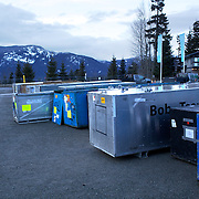 """Winter Olympics, Vancouver, 2010.Bobsleigh containers outside the venue during the Bobsleigh Four-man competition  at The Whistler Sliding Centre, Whistler, during the Vancouver Winter Olympics. 25th February 2010. Photo Tim Clayton..'BOB'..Images from the Four-man Bobsleigh Competition. Winter Olympics, Vancouver 2010..History was made at the Whistler Sliding Centre when the USA four-man bobsleigh team, led by Steven Holcomb took the Gold. The first time since 1948, a gap of 62 years, since the USA have won an Olympic Bobsleigh gold and they did it with their sleigh named """"Night Train""""...The four days of practice and competition show the tension, nervousness and preparation as the teams of hardened men cope with the challenge of traveling at average speeds of over 150 km an hour. Indeed, five teams had already pulled out of the event before the opening heats because of track complexity, speed and fear, and on the final day, another four teams did not start after six crashes in the first two heats...Teams warm up behind the start complex, warming muscles in the cold in preparation for the explosive start. Many teams prepare in silence, mentally preparing themselves as they wait at the top of the run, in the bobsleigh sheds and the loading areas for their turn. When it's time to slide each team performs it's own starting ritual, followed by the much practiced start out of the blocks for just over four seconds, the teams are then in the hands of the accomplished drivers as they hurtle down the track for just over fifty seconds...Spectators clamber for the best position on track to see the sleighs for a split second, many unsuccessfully try to capture the moments on camera, The rumble of the sleigh is heard then the crowds gasp as it hurtles past in a blur...The American foursome of  Steven Holcomb, Justin Olsen, Steve Mesler and Curtis Tomasevicz finished with a pooled four-heat time of 3min 24.46sec. The German team led by Andre Lange won the Silver Medal in a combin"""
