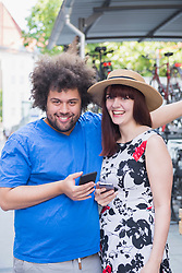 Portrait of happy couple using mobile phones in city