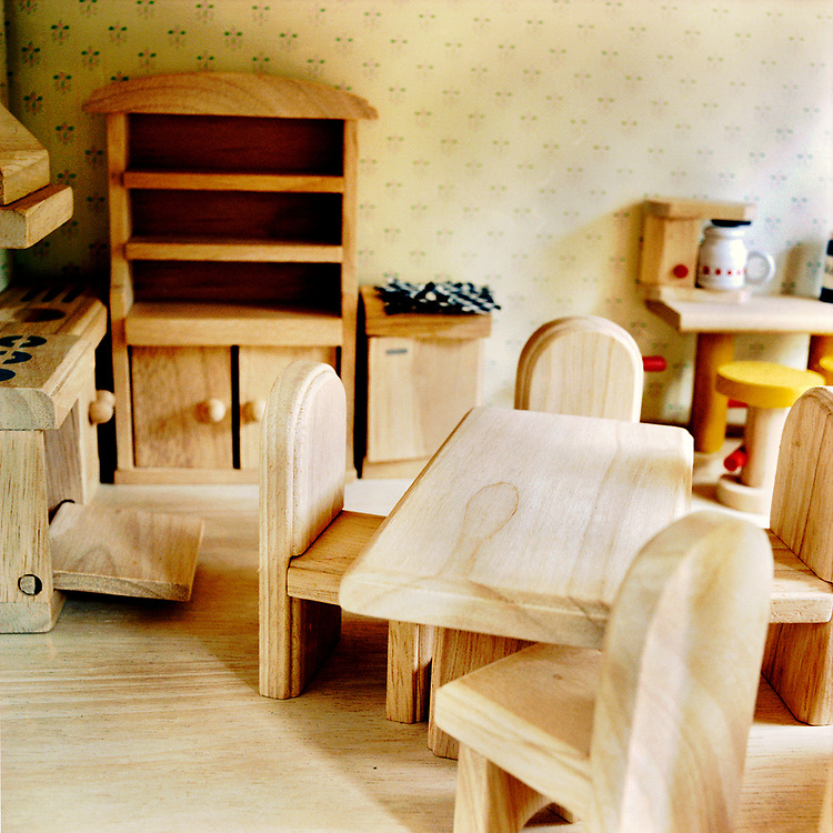 The kitchen of a wooden doll house, with a wooden table and chairs on the right, the appliances on the left, and a counter and stool in the right background. There is wallpaper that looks like a fleur de lys pattern