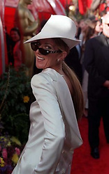 Pop star Celine Dion arrives at the 71st annual Academy Awards in Los Angeles, California, wearing a white Christian Dior backwards tuxedo and matching oversized fedora, with diamond-encrusted Raybans.