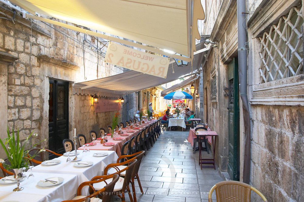 View the Prijeko street with restaurants with outside seating long tables and chairs lining the street under sun shades Dubrovnik, old city. Dalmatian Coast, Croatia, Europe.