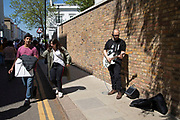 Busker playing guitar on Portobello Road Market in Notting Hill, West London, England, United Kingdom. People enjoying a sunny day out hanging out at the famous Sunday market, when the antique stalls line the street.  Portobello Market is the worlds largest antiques market with over 1,000 dealers selling every kind of antique and collectible. Visitors flock from all over the world to walk along one of Londons best loved streets.