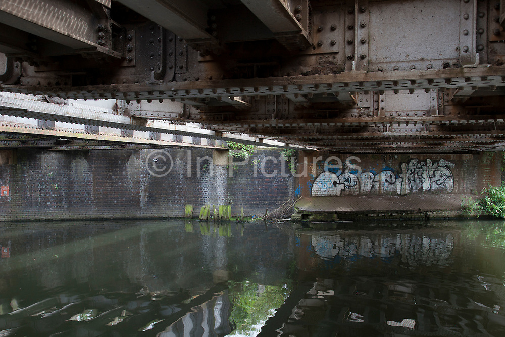 Scene along the Lea Navigational Canal in East London, UK. The River Lea is a major tributary of the River Thames. Much of the Lee Navigation is within Lea Valley Park, a multi-county regional park and open space preserve. Street are and graffiti is a regular sight along the canal.