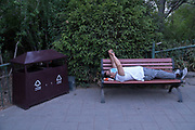 Beijing Jingshan Park man lying on park bench watching mobile telephone, wearing a pollution mask. China