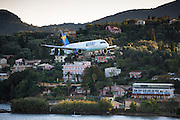 Thomas Cook Condor jet airplane tourist charter flight flying into Kerkyra, Corfu Town, ready for landing, Ionian Islands, Greece