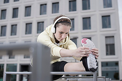 Young woman stretching her leg on railings and listening to music, Bavaria, Germany