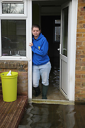 © Licensed to London News Pictures. 24/02/2014. Basingstoke, Hampshire, UK. Kirsty Campbell (23) standing at the back door of her house on Sperrin Close which she and her family have had to evacuate due to groundwater flooding in the Buckskin area of Basingstoke, Hampshire. The house, a council property operated by Sovereign, was first flooded on 8th February 2014. The council initially told her that they were unable to provide flood support for the area. The area is now being continuously pumped by tankers in an attempt to reduce the volume of flood water. Photo credit : Rob Arnold/LNP