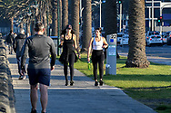 A pair of maskless women walk along the foreshore in Port Melbourne which is now a listed COVID hot spot in Melbourne on the 7th day the state wide COVID-19 lockdown that has been placed on the State of Victoria. (Photo by Michael Currie/Speed Media)