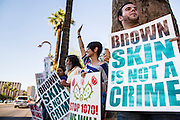 25 JUNE 2012 - PHOENIX, AZ:   LAURENT TAILLEFER (right), ANDREA BEGAY and other immigration supporters line the street in front of the Immigration and Customs Enforcement (ICE) offices in central Phoenix Monday. About 100 immigration supporters held a protest against ICE and continued deportations by the Obama administration. Protesters also celebrated the US Supreme Court decision to overturn most of SB1070, Arizona's tough anti-immigration law.     PHOTO BY JACK KURTZ