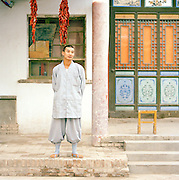 A young Buddhist monk outside a temple in Dunhuang, Gansu province, China