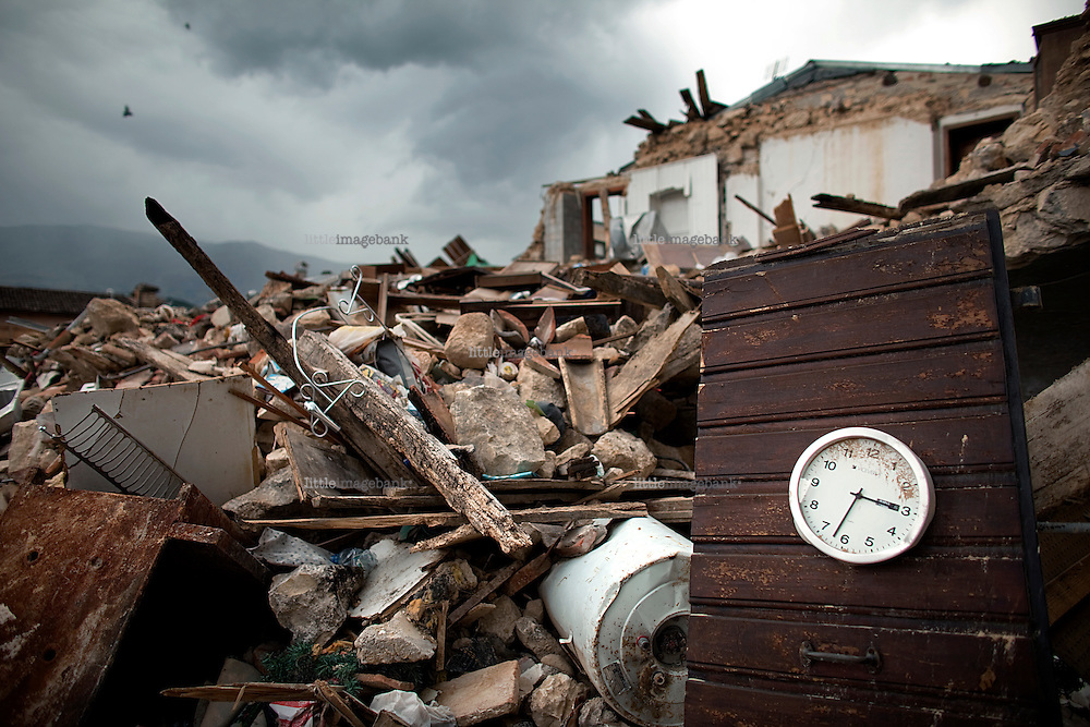 A wall mounted clock stands in the remains of a house in Onna. The clock has stopped on the exact time of the impact of the earthquake. On April the 6th 2009 at  3.32 a.m, a powerful earthquake struck a huge part of the Abruzzo region of central Italy killing 295 people. The dead were mainly in L'Aquila, a 13th century mountain city about 100 miles east of Rome that has a population of 80,000, and surrounding villages. This photodocumentary follows life in a small village outside L'Aqulia that lost 1/3 of its population in the quake. Onna was completely destroyed by the quake, and left the every  single citizen to live in army tents outside the village. Photo: Christopher Olssøn