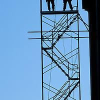 USA, Washington, Seattle, Silhouette of steelworkers assembling scaffolding under Aurora Bridge during seismic retrofit project