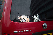 Comedy Scooby Doo and Shaggy sticker in the rear windscreen of a van. These famous lovable cartoon characters peer out of the back window as if hiding. London, UK.