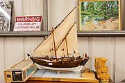Model sailing ship and other items on display inside an auction room