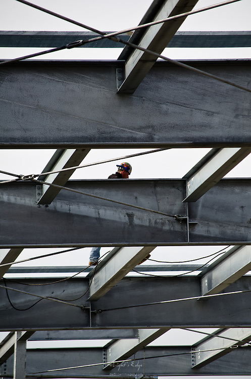 An iron worker walks on a grate during the steel frame construction which will support solar panels on top of the parking garage at Underwood Memorial Hospital in Woodbury, NJ.