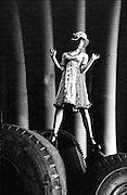 Standing on tires with sheet metal pipes and wearing a hat - One Woman Show