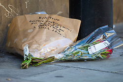 "Floral tributes to ""Tesfa"" lie on the road near the scene where a man in his 40s was stabbed on Latchmere Road in Battersea in the afternoon of July 3rd 2019, dying later that evening in hospital. London, July 04 2019."