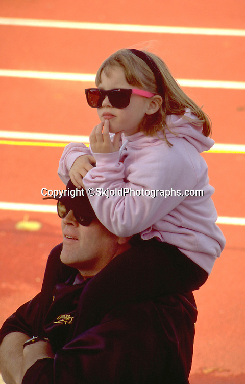 Thoughtful girl with sunglasses riding on dads shoulders at track meet age 28 and 5.  St Paul Minnesota USA
