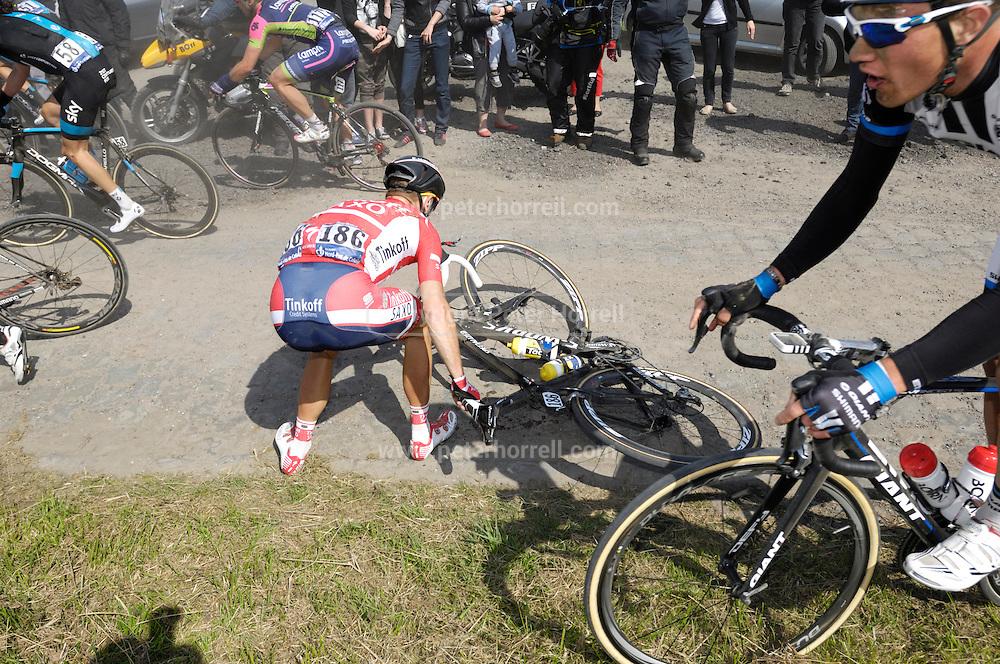 France, April 13th 2014: Saxo-Tinkoff's Michael Morkov (#186) picks his bike off the road following a crash at Pont Gibus, Wallers.