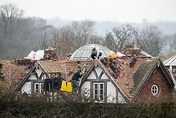 © London News Pictures. 24/03/2016. THE FIDDLER ON THE ROOF....Robert Fidler pictured removing tiles from the roof of a house he illegally built in Redhill Surrey. A court ordered Rob Fidler to demolish the property by June 2016 after it was built without planning permission and hidden from public view behind a haystack. Photo credit: Presspics/LNP