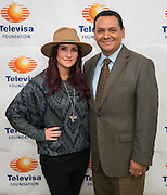 """Telenovela actress Dulce Maria, left, Ed Gonzalez, right, pose for a photograph following a Televisa Foundation """"Live the Dream"""" event at Burbank Middle School, December 9, 2013."""