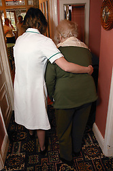 Carer helping to support an elderly woman walking; homecare for the elderly,