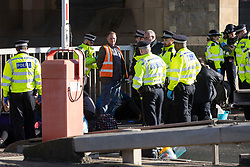 © Licensed to London News Pictures. 03/10/2021. London, UK. An activist from Insulate Britain is arrested at the entrance to the Blackwall tunnel after it was blocked by the group earlier this morning. Insulate Britain have successfully blocked various roads around the capital over a number of weeks, resulting in a court injunction banning them from going near the M25 motorway.  Photo credit: George Cracknell Wright/LNP